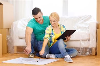 happy couple checking their checklist for moving home